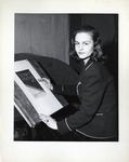 Student poses for a photograph at a drafting table by School of Practical Art