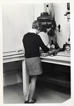 Photo Student Susan Anderson Using an Enlarger in The Darkroom by Art Institute of Boston